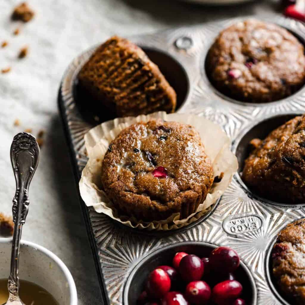 paleo cranberry orange muffins in a muffin tray