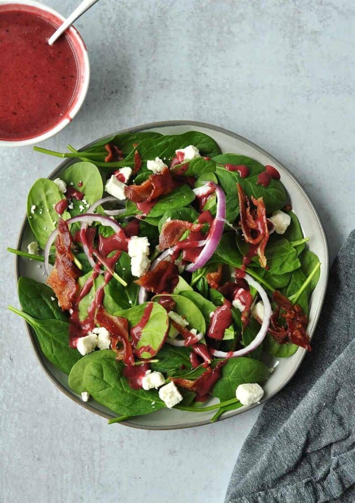 A refreshing spinach salad just in time for spring. A sweet-tart blueberry vinaigrette dresses tender fresh spinach leaves, briny feta cheese, savory bacon and aromatic purple onions. The perfect side dish for any meal.