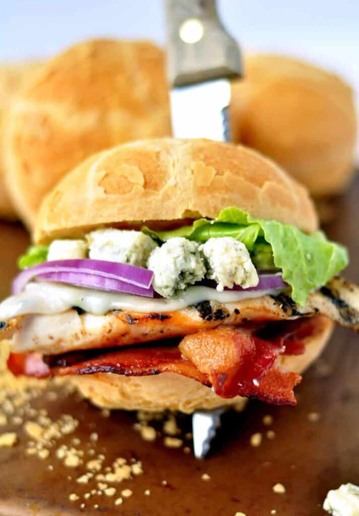 Bacon and Bleu Grilled Chicken Sandwich assembled with knife holding it together.