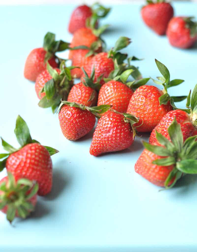 a row of bright red strawberries on a blue background