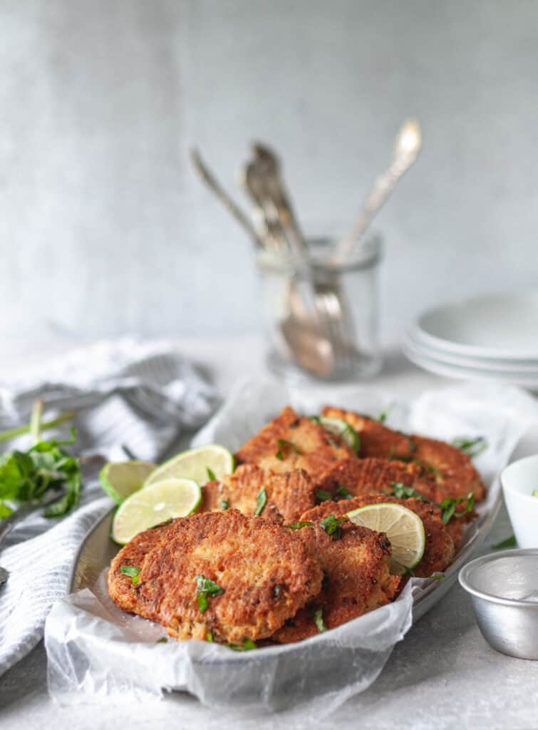 tray of gluten free salmon patties with limes around it and plates in the background