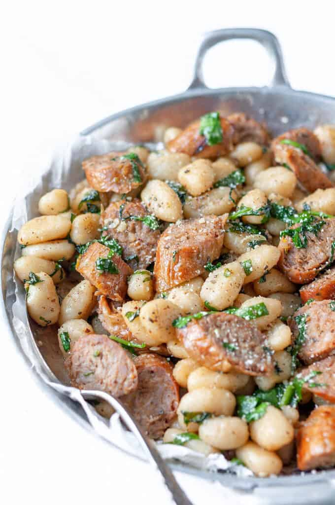 gnocchi and sausage with a spoon resting in silver bowl
