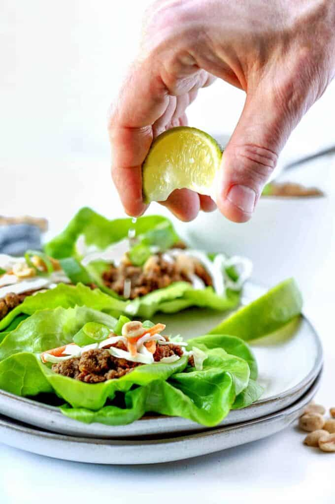 lettuce wraps with lime being squeezed over top