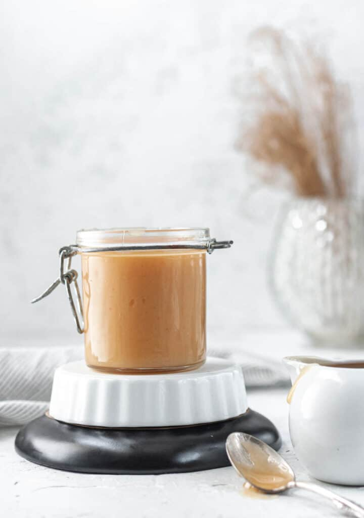 vegan caramel in a jar with a spoon and creamer cup next to it