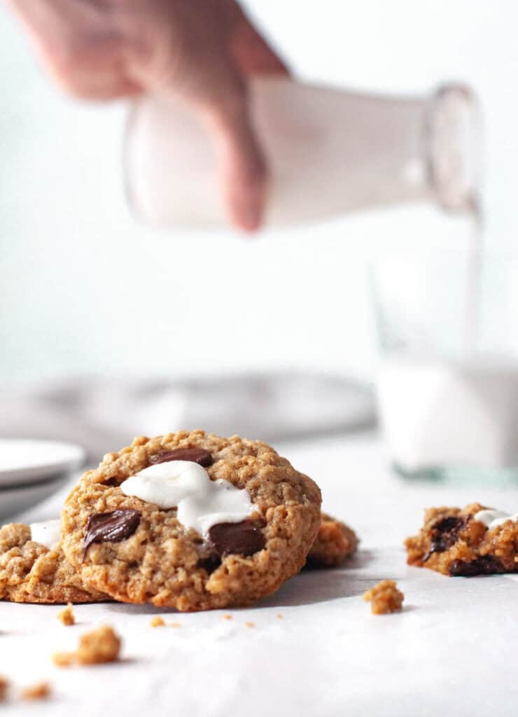 one cookie with milk being poured in the background