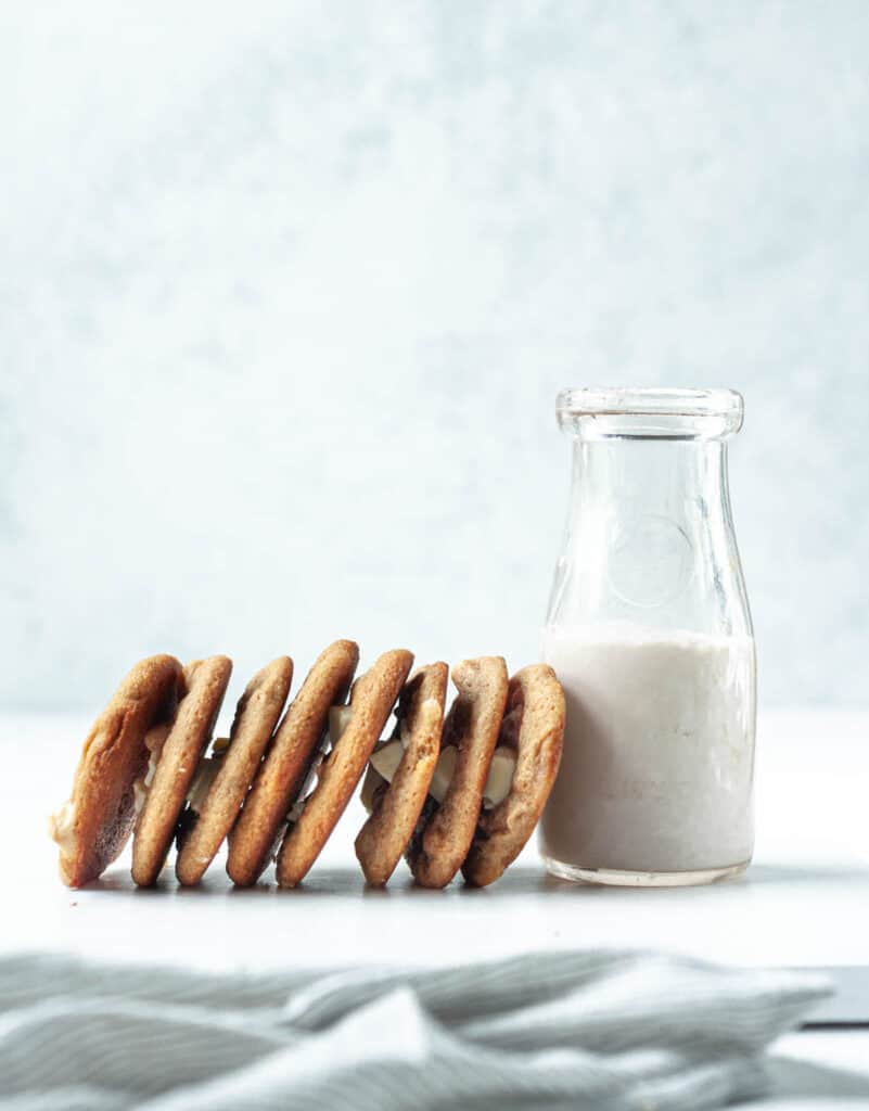 a row of cookies stacked on their side leaning on milk