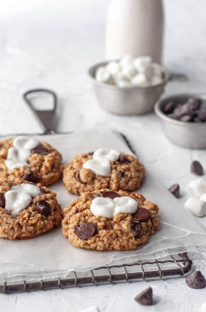 four cookies on a cooling rack with milk in the background