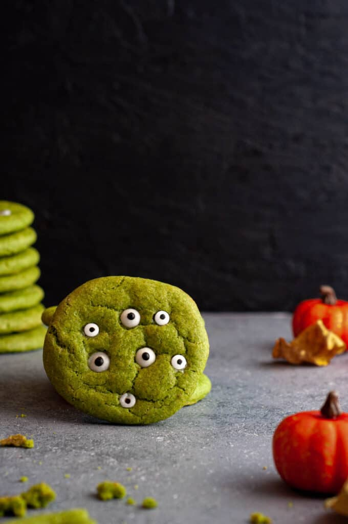 monster cookie with a stack of cookies behind it and two pumpkins