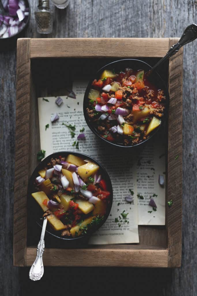 two bowls of beef and potato mexican soup in a wood box
