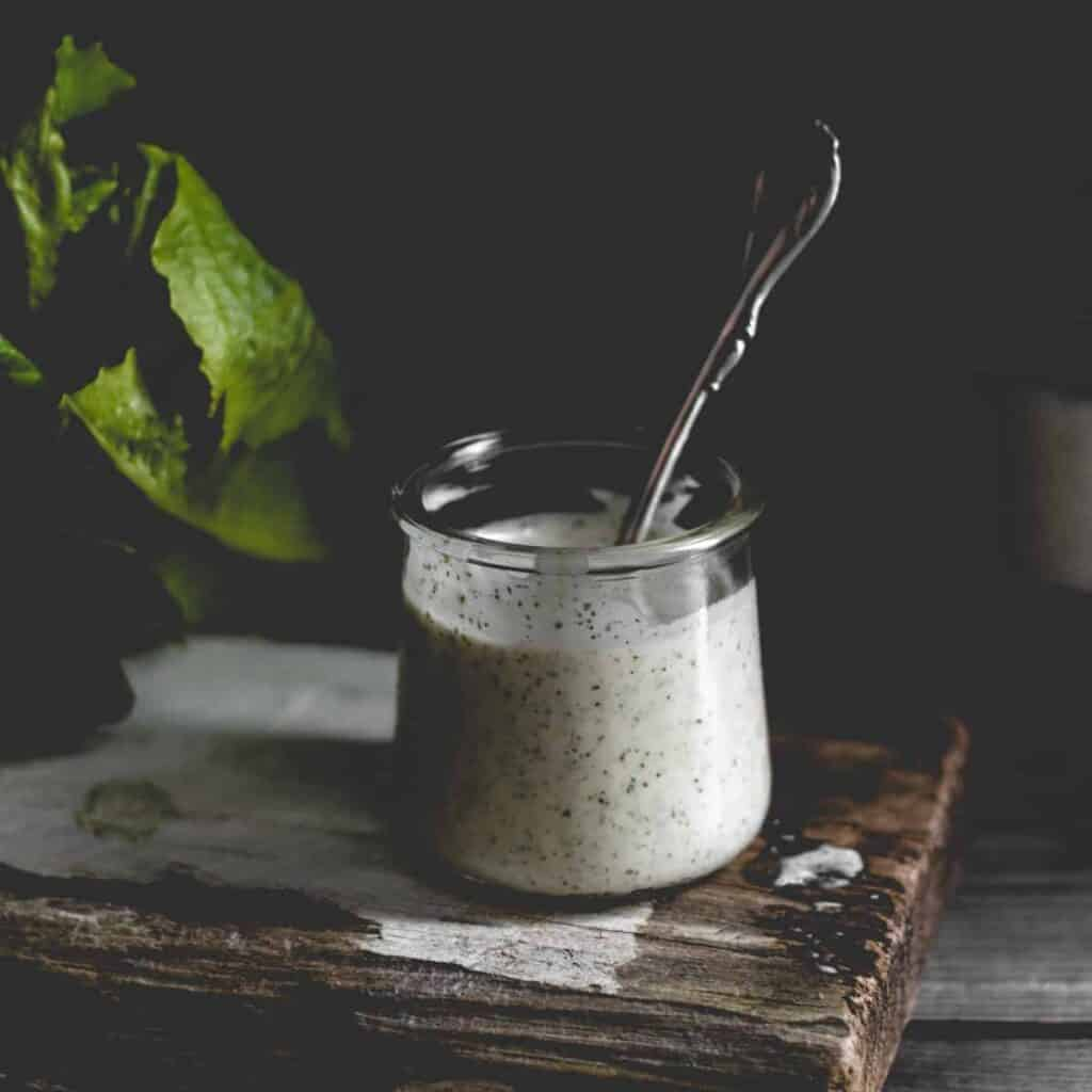 close up ranch dressing with a spoon in glass container