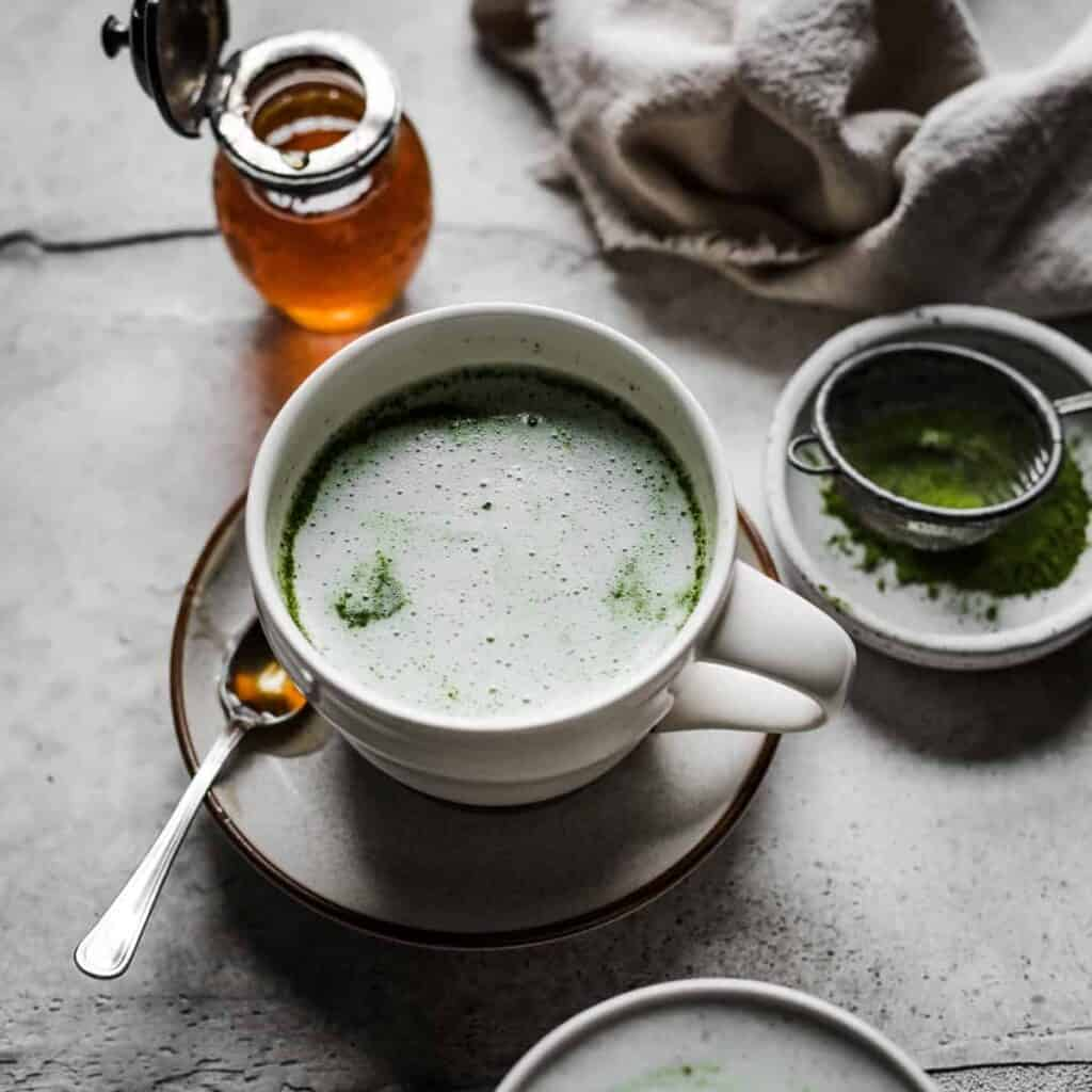 cup of matcha with spoon and honey in background