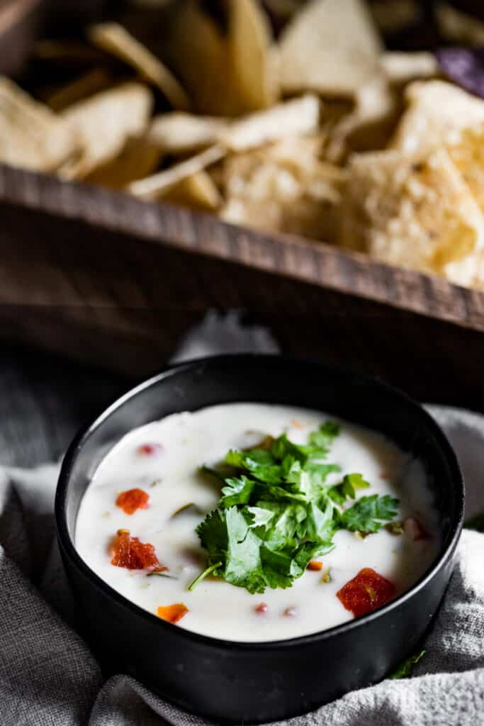 bowl of gluten free queso blanco with chips in the background