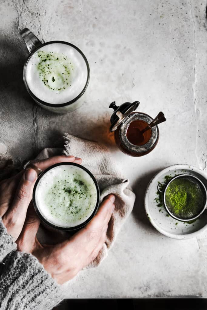two cups of matcha collagen latte's on a table overhead view