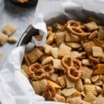 close up photo of chex mix in a round container