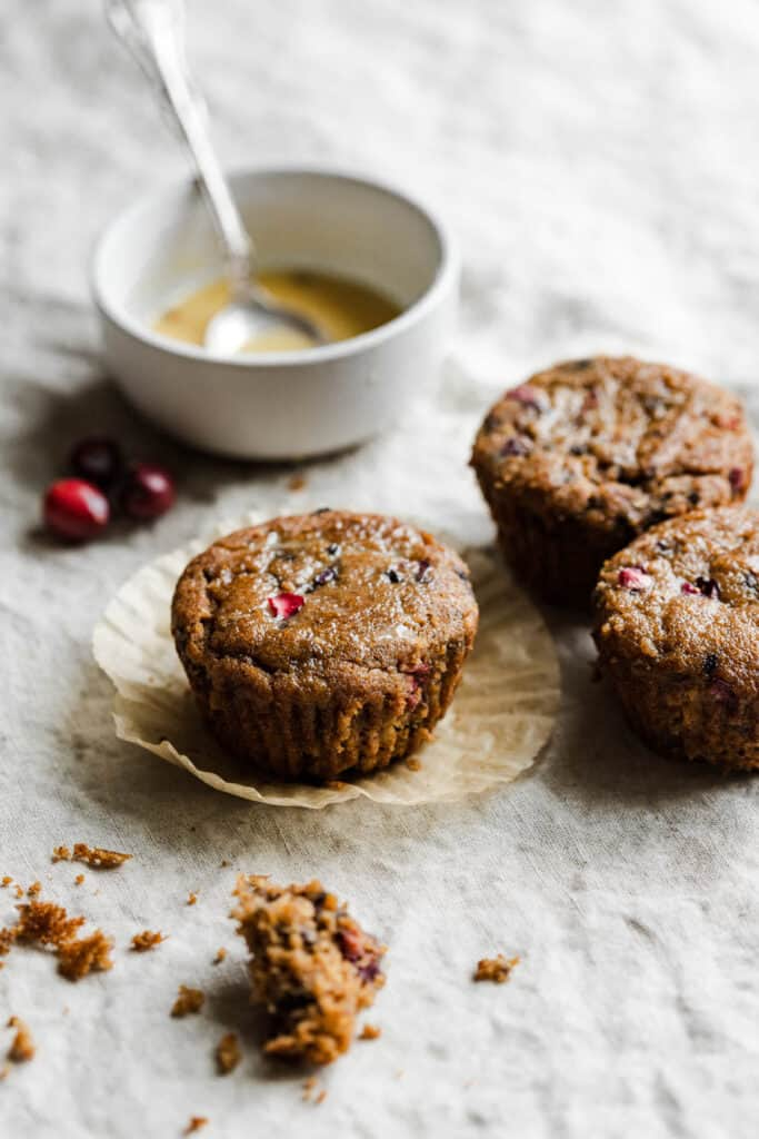 3 paleo cranberry orange muffins with the glaze in the back