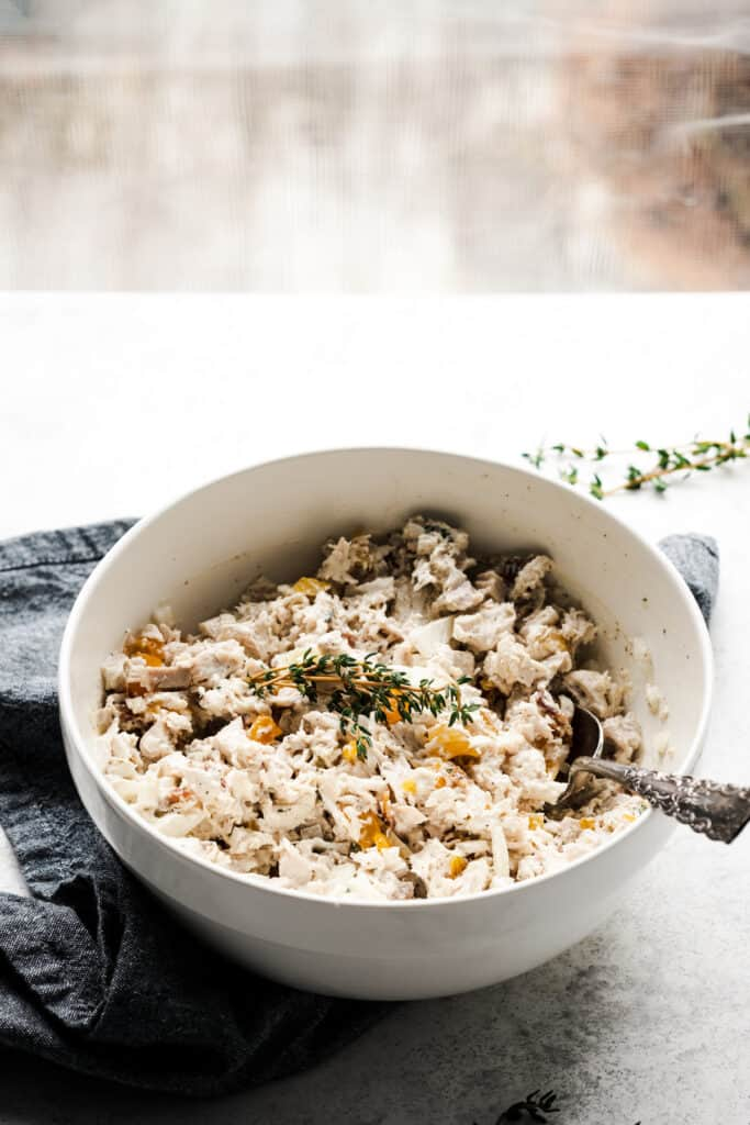 bowl of mixed thyme bacon apricot chicken salad on a white backdrop and a window in the background