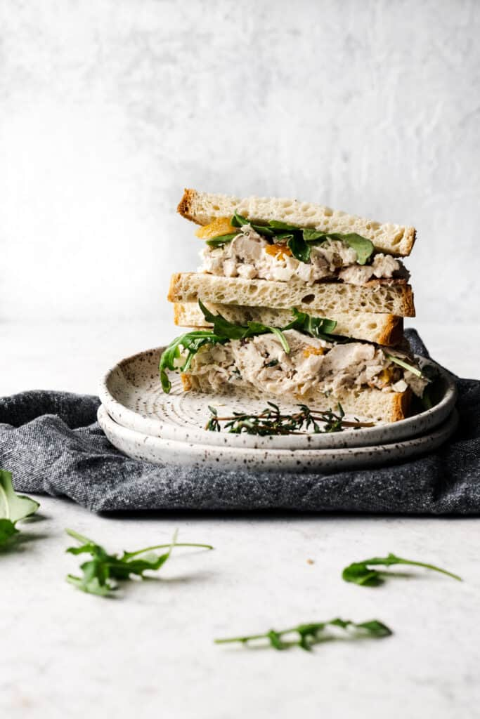 chicken salad sandwiches stacked on top of each other and on two plates with a grey towel