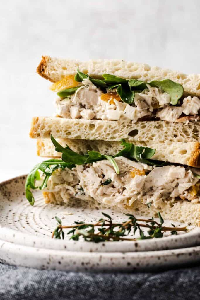 Close up shot of the thyme bacon apricot chicken salad on bread and stacked on top of each other