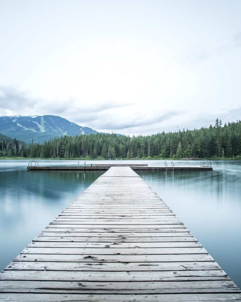 A DOCK AND LAKE WITH MOUNTAINS IN THE BACK