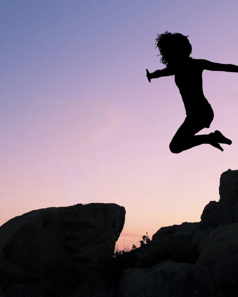 A PERSON JUMPING OFF A ROCK