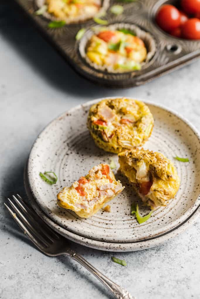 2 canadian bacon egg muffins with tomatoes and green onion on a plate