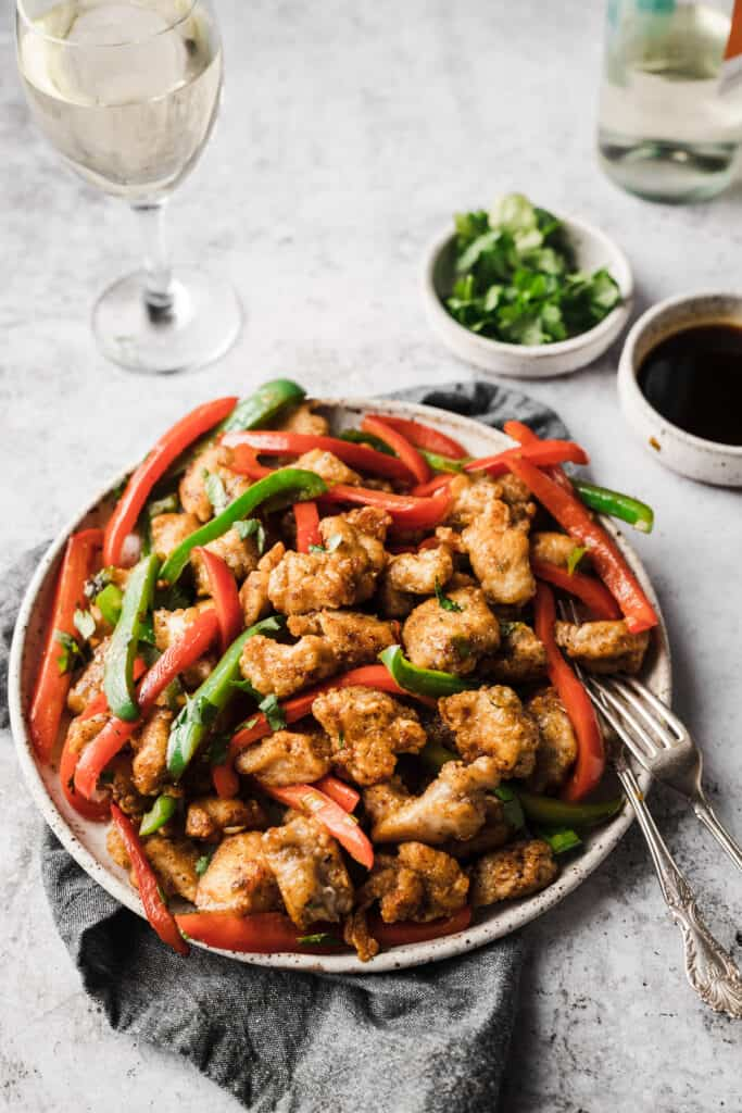 large plate of salt and pepper chicken with wine glass