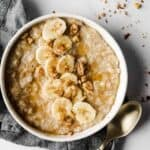 up close shot of creamy banana oatmeal with gold spoon