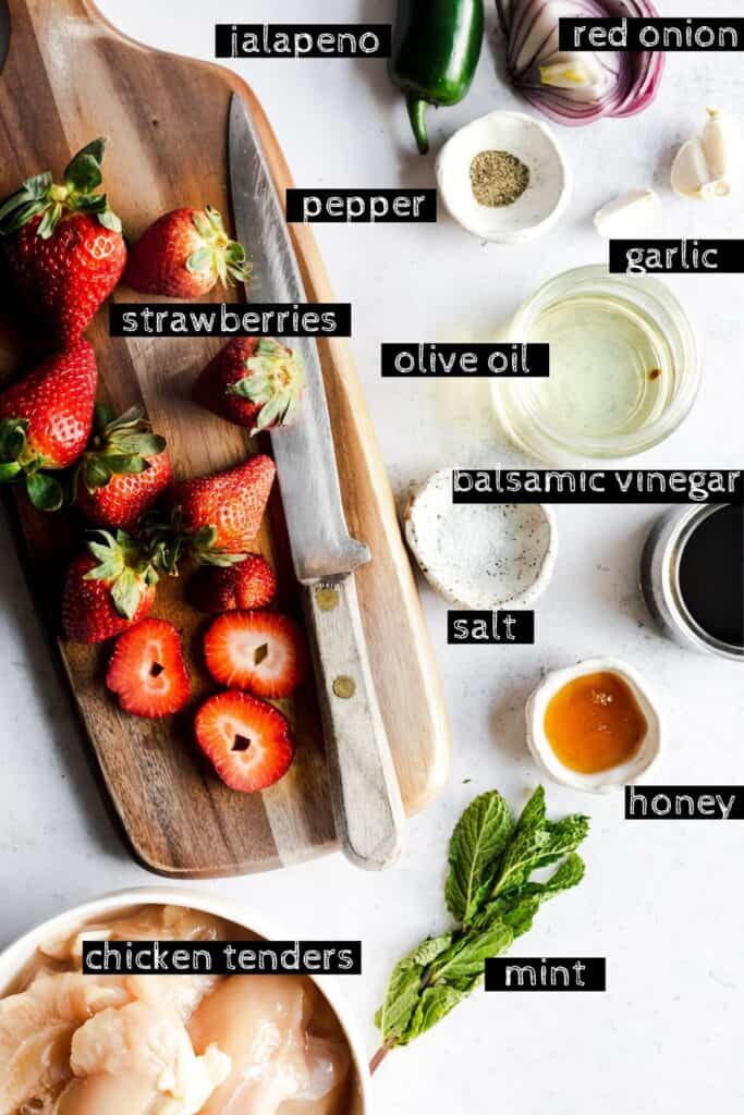 all of the ingredients labeled- strawberries, jalapeno, red onion, pepper, garlic, salt, olive oil, balsamic vinegar, honey, mint, chicken