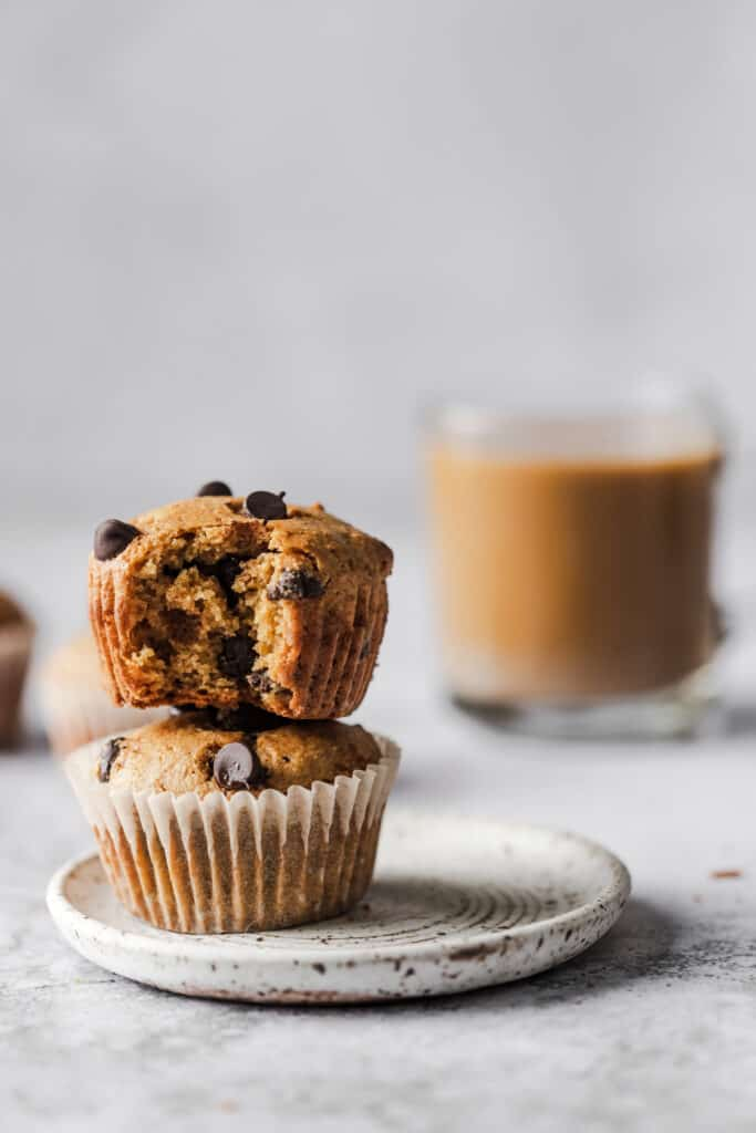 two muffins stacked on each other with coffee in the background