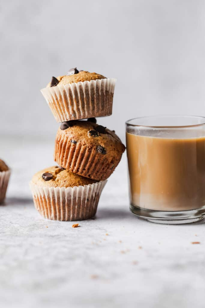 three muffins stacked leaning on a cup of coffee