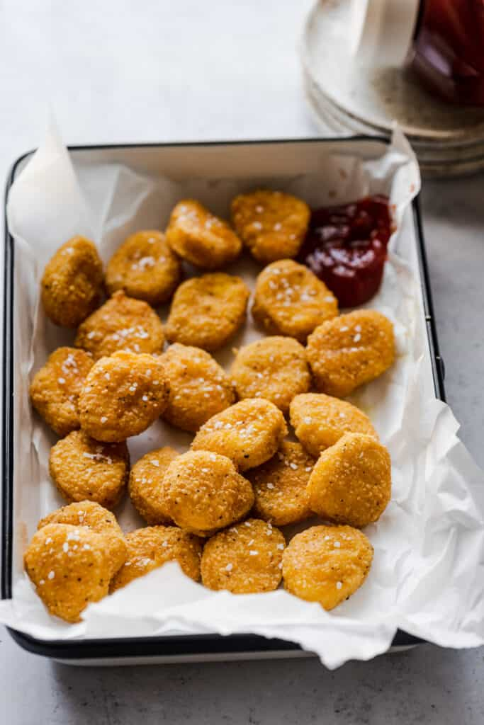 tray of chicken nuggets with ketchup in the background