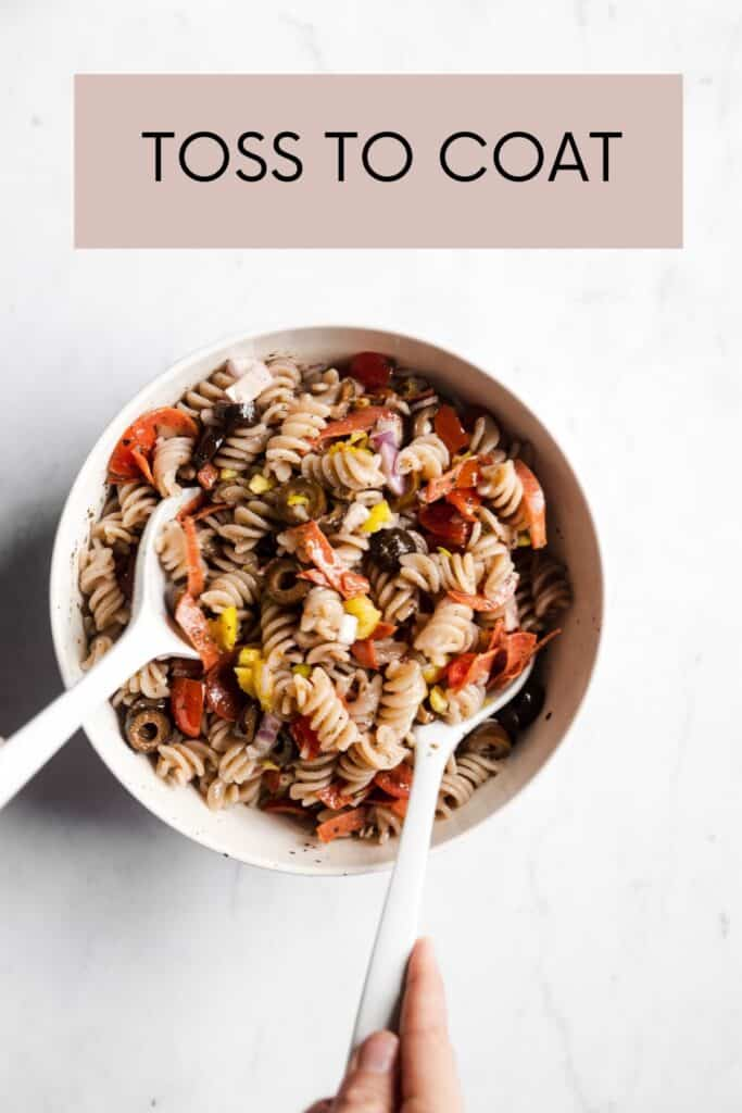 pasta salad in white bowl with white tongs tossing the salad