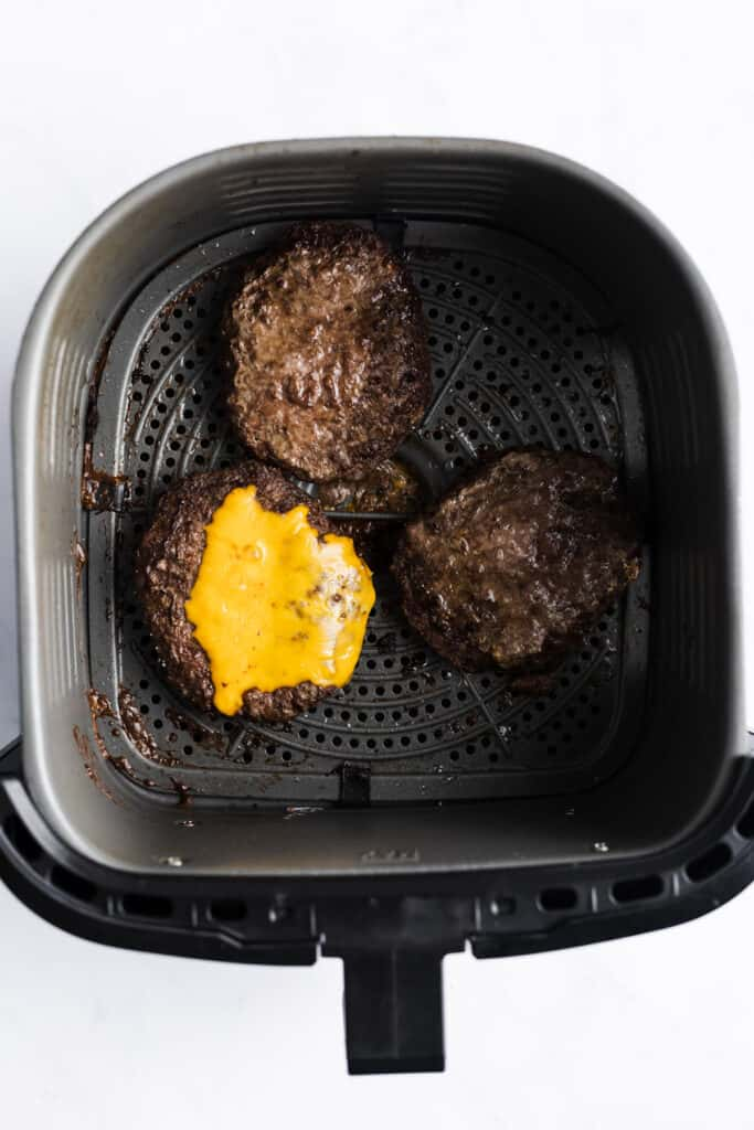 3 BURGERS IN AN AIR FRYER BASKET ONE HAS CHEESE