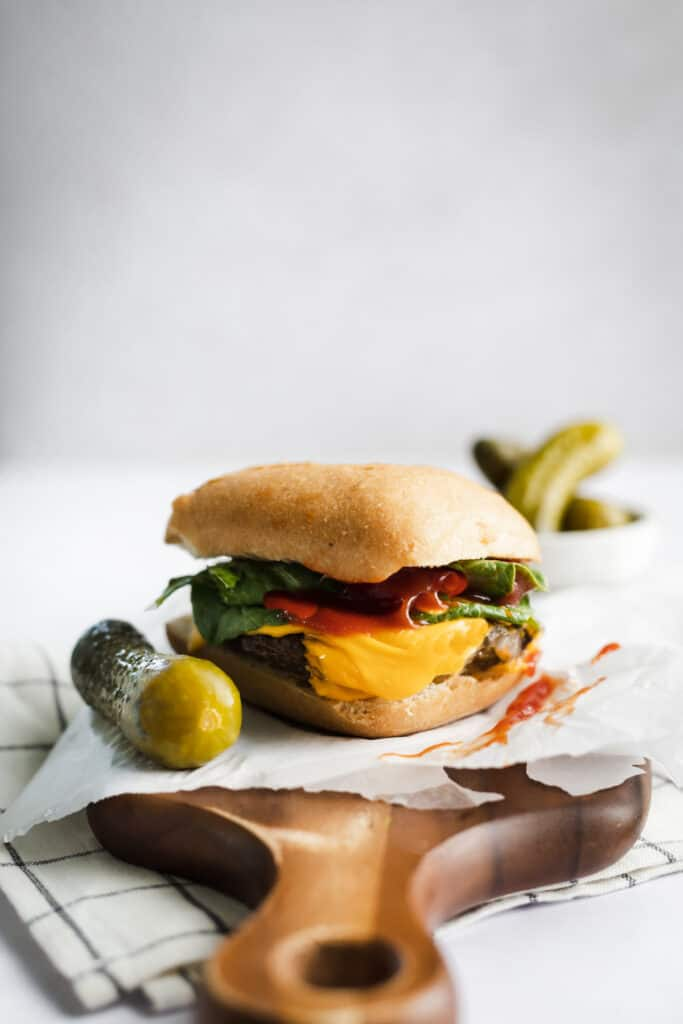 CHEESE BURGER ON A WOOD CUTTING BOARD WITH PICKLES