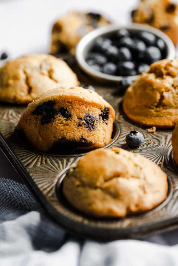 muffins in a muffin pan with blueberries in the background