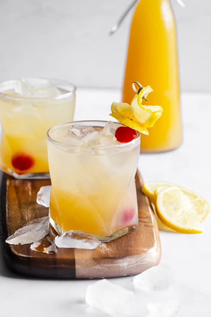 two drinks on a wood board with ice on the board and peach juice in the background