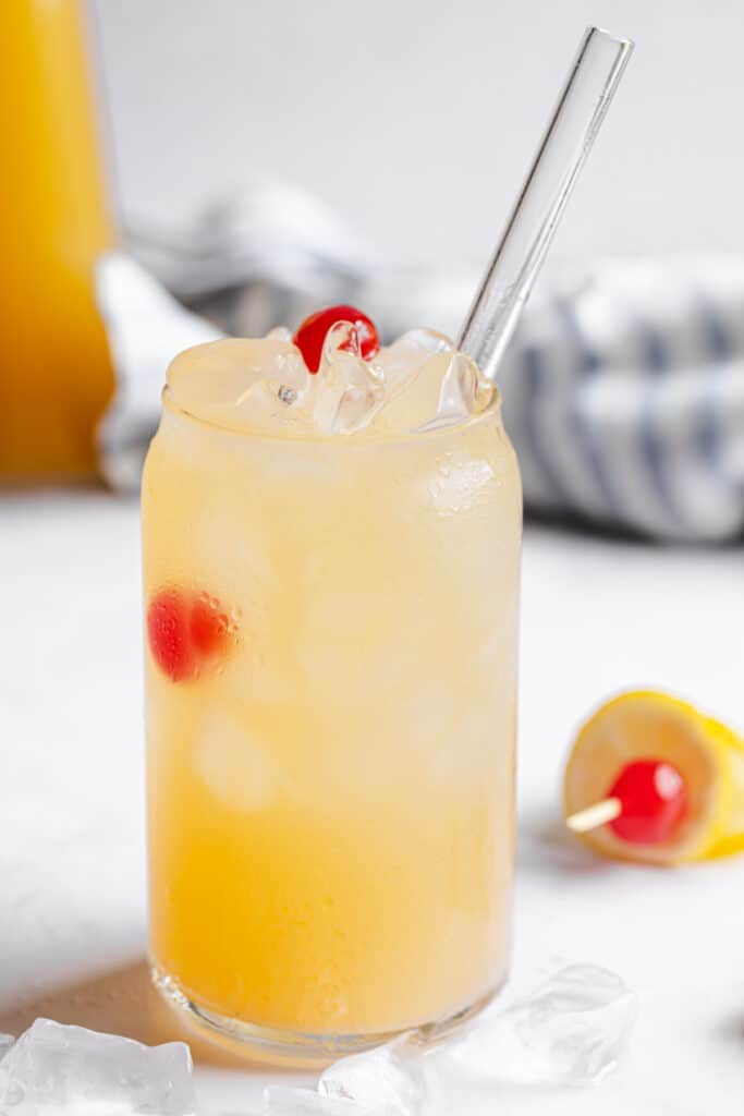 head on shot of summery mocktail with garnish on table and a blue towel in background