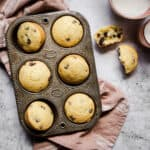 6 muffins in an antique muffin tin, with a a muffin cut open by them.