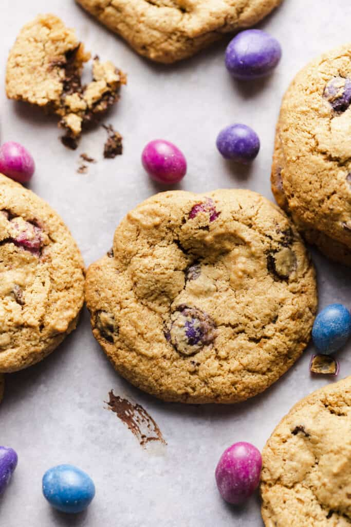 6 cookies on a grey background with mm's around it and chocolate smears