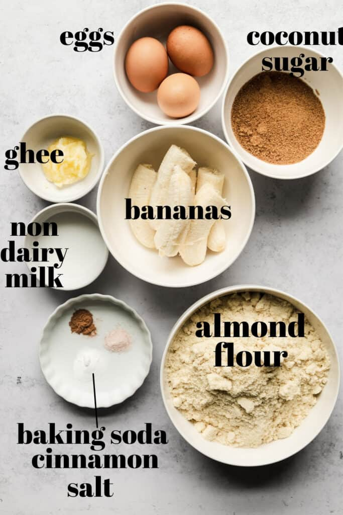 Ingredients for muffins all in separate white bowls.