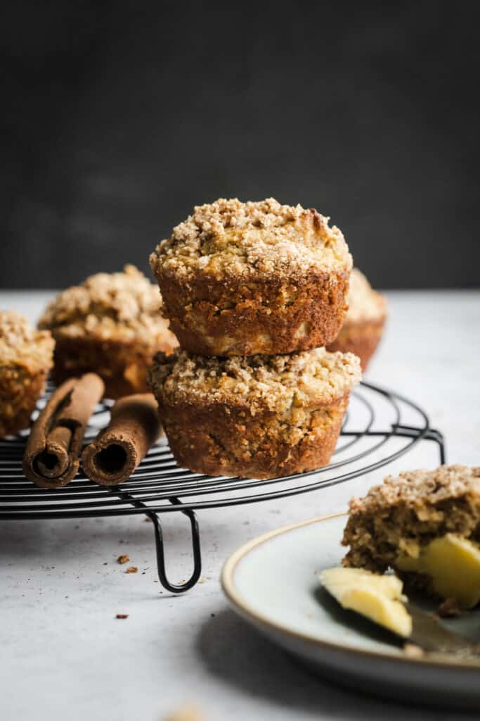 Two muffins stacked on top of each other on a black wire cooling rack.