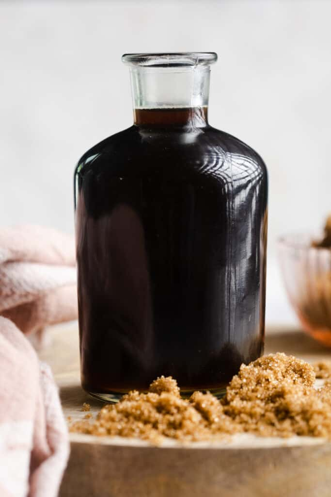 A close up image of head on shot of brown sugar simple syrup in a glass bottle.