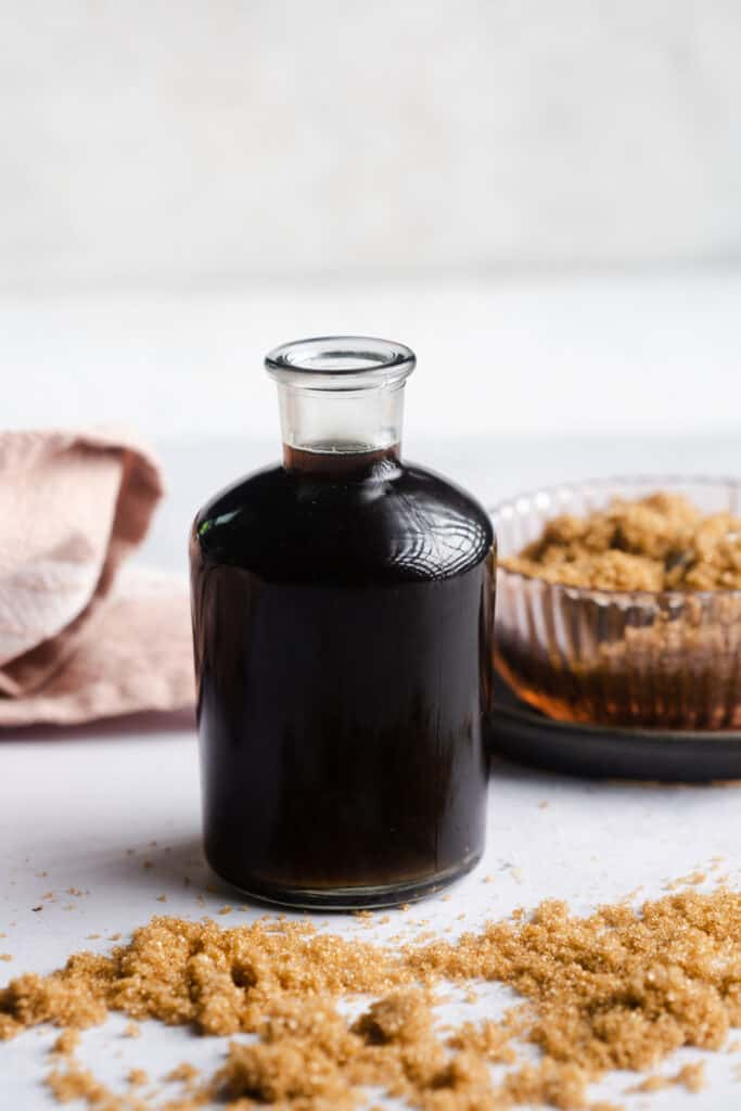 A glass bottle of brown sugar simple syrup with brown sugar scattered in front.