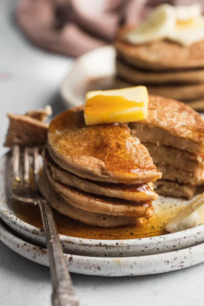 A close up image of a stack of pancakes with a bite cut out.